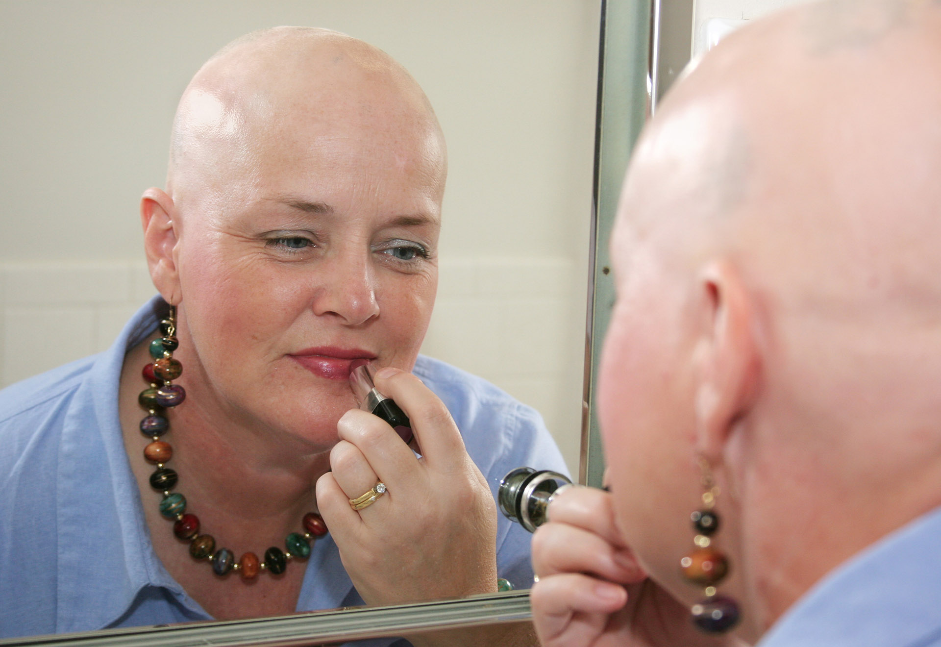 A woman bald from a health problem putting on makeup in the mirror.