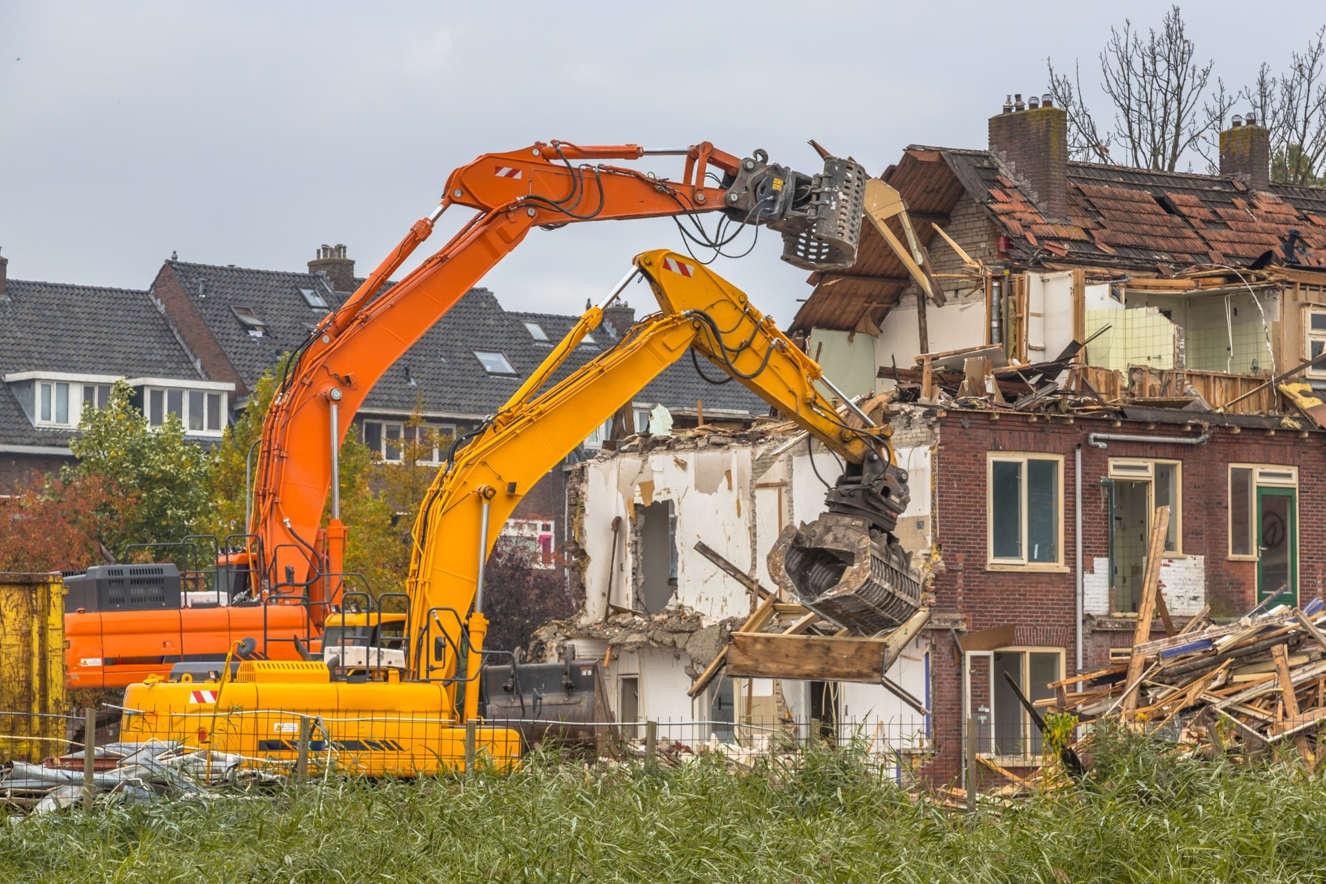 Two Demolition cranes demolishing old row of houses in the Netherlands